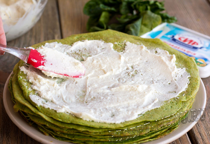 Намазать зеленые блины сырной начинкой